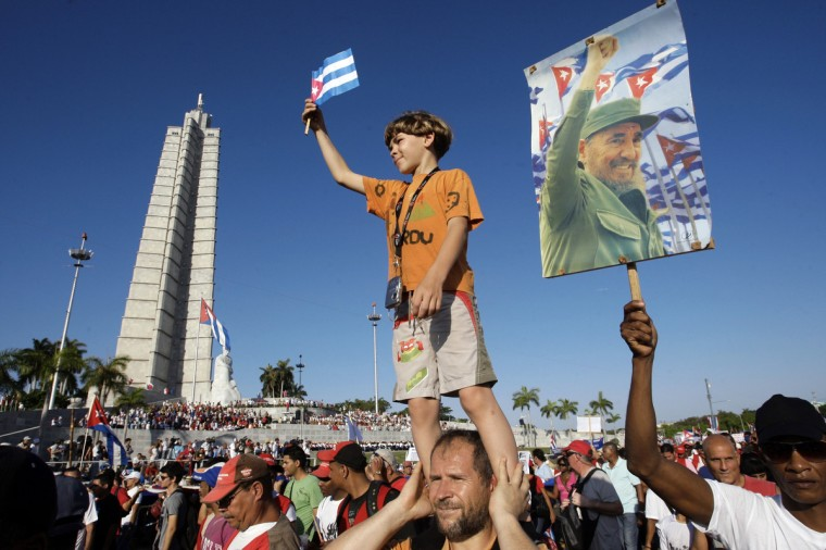 A man carries a boy on his shoulders at the May Day parade in Havana's Revolution Square. Many marched through Havana's Revolution Square on Tuesday in a May Day parade that affirmed the government's intention of assuring a communist future for the Caribbean island. (Reuters)