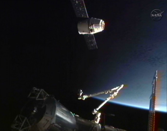The SpaceX Dragon commercial cargo craft is seen with the International Space Station's Canadarm2 in the foreground as it holds position 30 meters (98 ft.) from the station as the crew of the ISS conducts final tests before the grapple and docking of the capsule in this image captured from NASA TV. (NASA TV/Reuters)