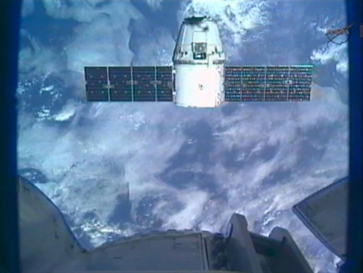 The SpaceX Dragon commercial cargo craft is seen with part of the International Space Station in the foreground as it holds position 30 meters (98 ft.) from the station as the crew of the ISS conducts final tests before the grapple and docking of the capsule in this image captured from NASA TV. (NASA TV/Reuters)