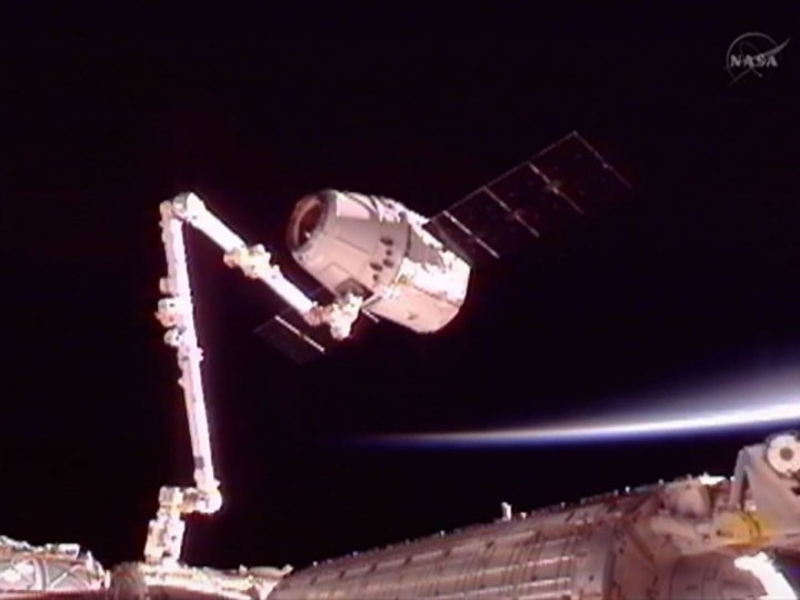 The SpaceX Dragon commercial cargo craft is moved into position for docking with the International Space Station using the station's Canadarm2 in this image captured from NASA TV. (NASA TV/Reuters)