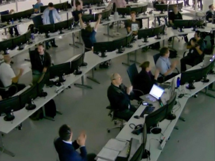 Flight controllers clap and celebrate at SpaceX mission control in Hawthorne, California as the Dragon commercial cargo craft is captured by the crew aboard the International Space Station using the Canadarm2 in this image from NASA TV. (NASA TV/Reuters)