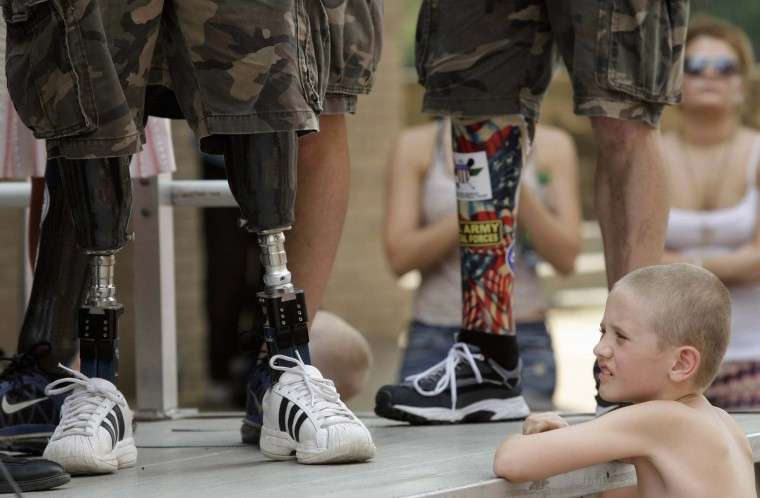 A child looks at the prosthetic legs of Wounded Warrior Amputee Softball team members during a Memorial Day Parade in Binghamton, New York May 28, 2012. Wounded Warrior Amputee Softball team members are U.S. veterans of the Iraq and Afghanistan wars who lost limbs during their time of service. (Gary Cameron/Reuters)