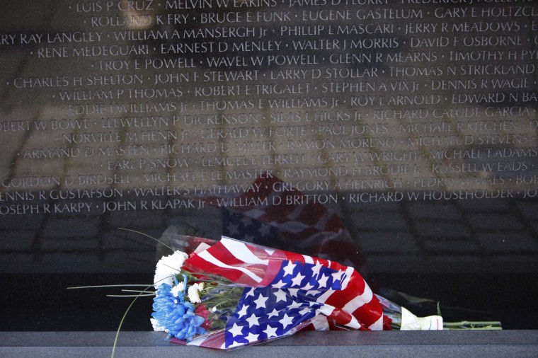 Flowers are placed at the Vietnam Veterans Memorial wall, which is etched with the names of more than 58,000 U.S. servicemen and women who died in the war, on Memorial Day in Washington May 28, 2012. (Yuri Gripas/Reuters)