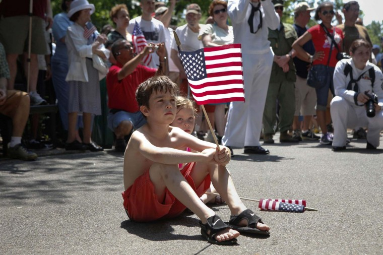 A boy waves a United States flag during a ceremony following a Memorial Day Parade in the Inwood Neighborhood of New York, May 28, 2012. (Andrew Burton/Reuters)