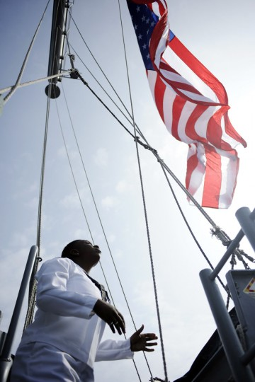 U.S. Navy quarter master Krystal Jones raise a flag on the USS Wasp as the amphibious assault ship enters into New York Harbor for Fleet Week May 23, 2012. (Keith Bedford/Reuters)