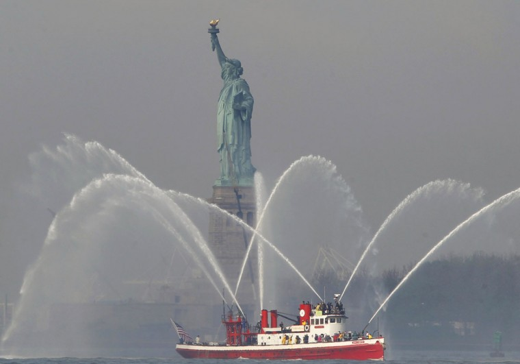 A New York City Fire Department fireboat turns on the hoses by the Statue of Liberty in New York Harbor while participating in the 25th annual Fleet Week celebration in New York, May 23, 2012. (Brendan McDermid/Reuters)