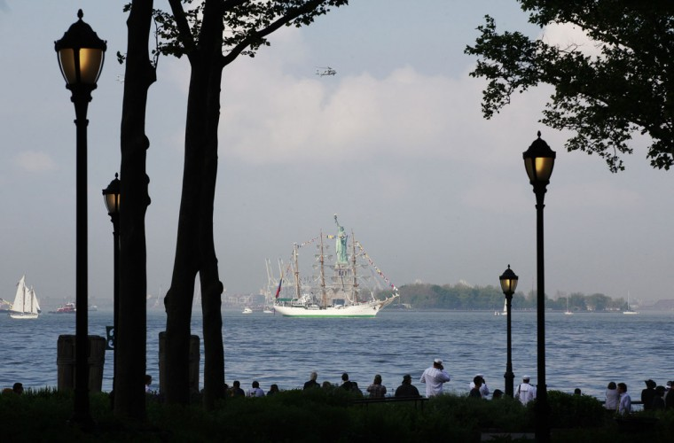 People watch as the tall ship BAE Guayas from Ecuador passes the Statue of Liberty in New York Harbor, while arriving for the 25th annual Fleet Week celebration in New York, May 23, 2012. (Brendan McDermid/Reuters)