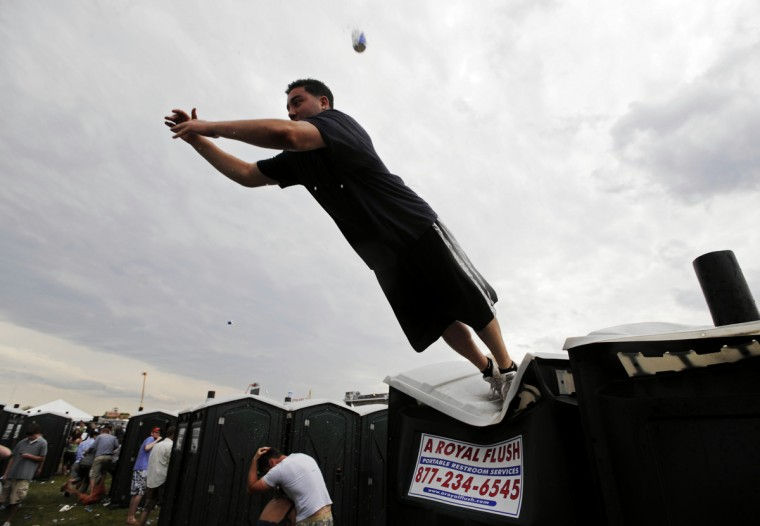 The running of the urinals continued in 2008 even though they were spaced apart in the infield. A port-a-john runner tries to make a leap from one row to another -- and fails as he falls short. (Christopher T. Assaf/Baltimore Sun)