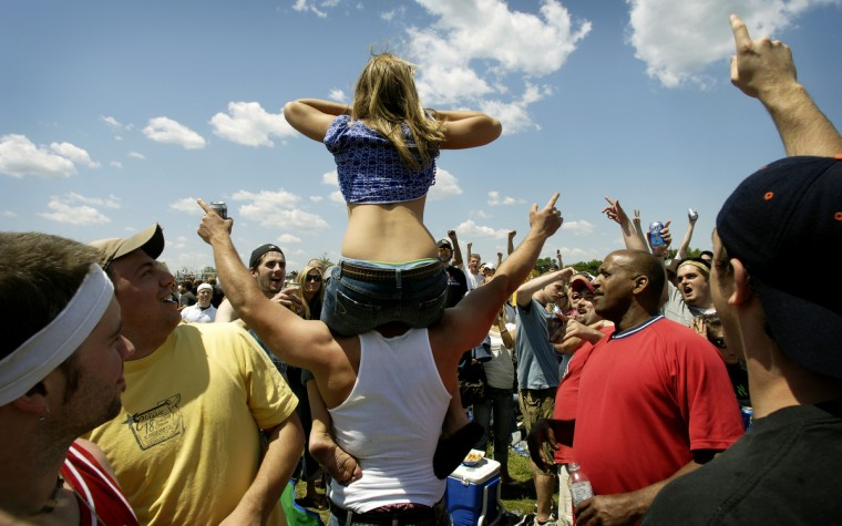 To the cheers of those surrounding her, a young woman bares herself to the crowded infield of Pimlico in 2007. (Christopher T. Assaf/Baltimore Sun)