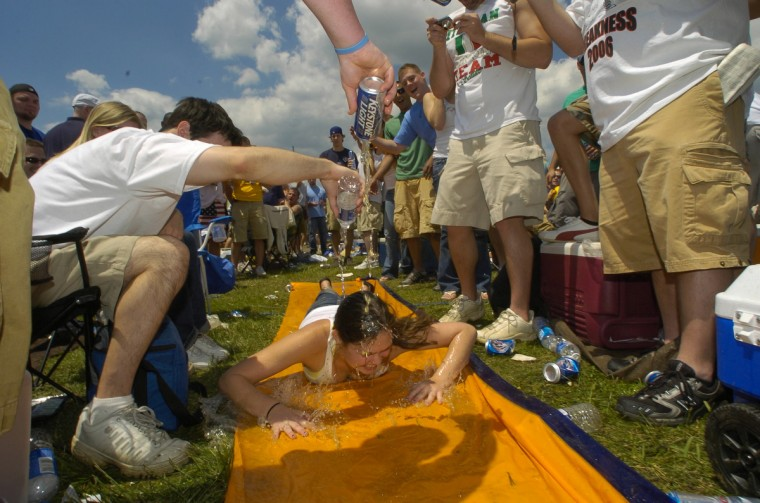 A woman heads down a slip 'n slide and is doused with beer to earn a free drink in the infield in 2006. (John Makely/Baltimore Sun)