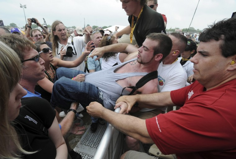 A race goer is escorted out of the infield by security personnel after a fight during the ZZ Top concert in 2009. (Lloyd Fox/Baltimore Sun)