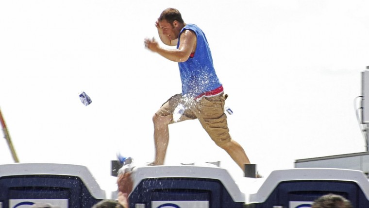 A Preakness infield spectator runs on the top of a line of port-a-johns while people hurl cans and bottles of beer at him in 2007. (Karl Merton Ferron/Baltimore Sun)
