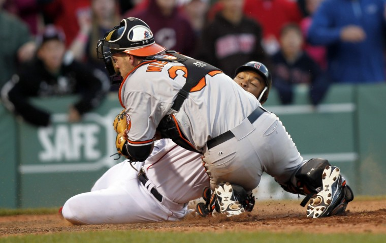Boston Red Sox center fielder Marlon Byrd (23) is tagged out at home plate by Baltimore Orioles catcher Matt Wieters (32) during the 16th inning at Fenway Park which kept the game tied and allowed the Orioles to go on top in the 17th inning and win the game. (Greg M. Cooper/USPW photo)