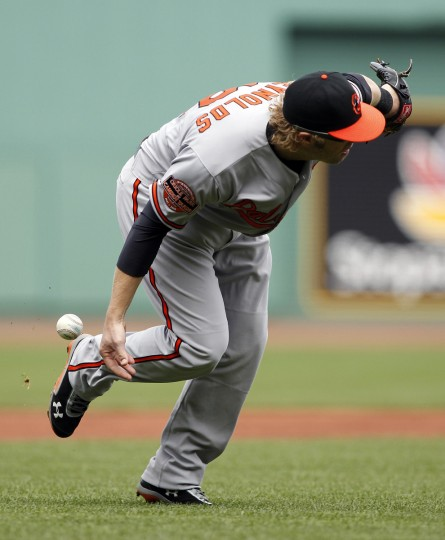 Baltimore Orioles third baseman Mark Reynolds (12) commits an error during the first inning against the Boston Red Sox at Fenway Park. Mandatory Credit: Greg M. Cooper/USPW photo)