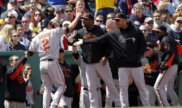 Baltimore Orioles shortstop J.J. Hardy (2) is welcomed to the dugout after hitting a home run against the Boston Red Sox during the third inning at Fenway Park. (Greg M. Cooper/USPW photo)