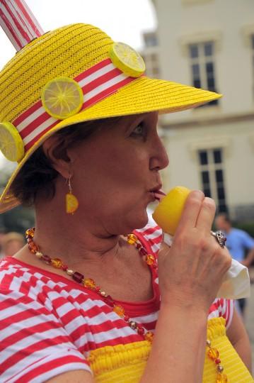Julia Johnson of Elkridge enjoys the sweet tang of a lemon stick while watching the Grand Hat Contest. (Karl Merton Ferron / Baltimore Sun Staff)
