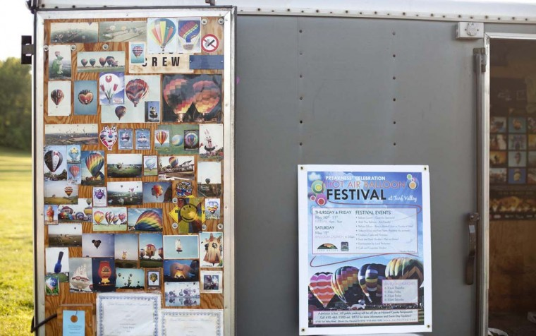 Wes and Kathy Remley of Quakertown, Pa., display photographs from various balloon festivals on the doors of the trailer that they use to transport their balloon, Kaleidoscope. The Remleys have attended the Preakness Celebration Balloon Festival every year. (Sarah Pastrana/Patuxent Homestead)