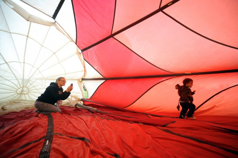 Candice Ngo of Silver Spring, left, tries to capture video of her two year old son Silas playing inside a walkabout balloon, retired from flying, owned by A Beautiful Balloon company from Parsippany, N.J. (Brian Krista/Patuxent Homestead)
