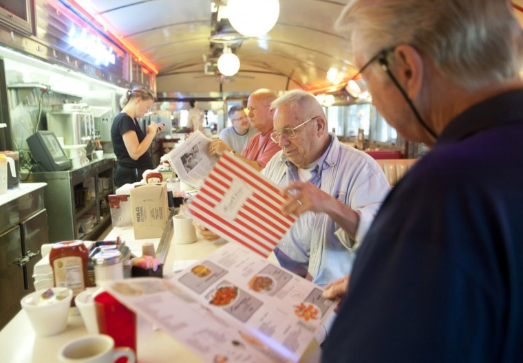 (R-L) Rich Dietrich and Dave Eberhart, both of Ellicott City, look at old menus from the '80s while John Miller, also of Ellicott City, reads the newspaper at the Forest Diner on May 21. Waitress Ellen Jackson (not pictured) found the old menus when she was cleaning and gave them to longtime customers as mementos. The diner will close at the end of the day on May 28. Dietrich says he has been coming to the diner since 1969. (Sarah Pastrana/Patuxent Homestead)