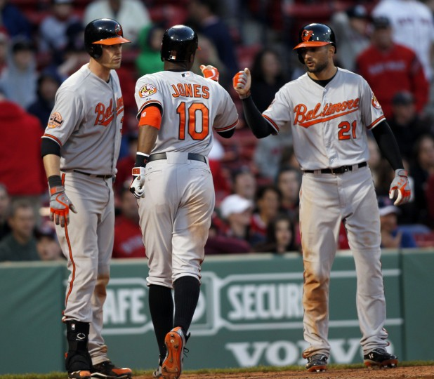 Baltimore Orioles center fielder Adam Jones (10) is welcomed to home plate by Baltimore Orioles catcher Matt Wieters (32) and right fielder Nick Markakis (21) after hitting a three run home run during the 17th inning at Fenway Park. (Greg M. Cooper/USPW photo)