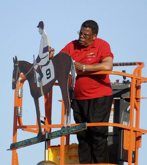 Pimlico track worker paints the silk color of Mario Gutierrez on the weathervane on the winner's circle's cupola. (Gene Sweeney Jr./Baltimore Sun)