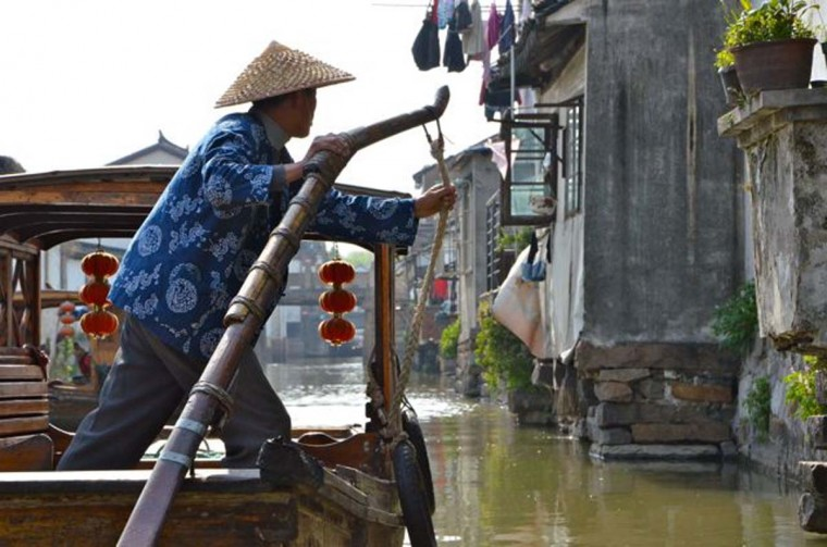 """The couple also took a day trip to Suzhou, one of a number of """"water towns"""" about an hour or two from Shanghai. Above, a boatman in Suzhou. (Credit: Scott and Pam Gorsuch)"""