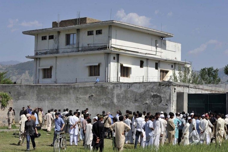 Pakistani media personnel and local residents gather outside the hideout of al-Qaida leader Osama bin Laden following his death by American Special Forces. The bullet-riddled Pakistani villa that hid bin Laden from the world was put under police control, as media sought to glimpse the debris left by the U.S. raid that killed him.(Aamir Qureshi/AFP/Getty Images)