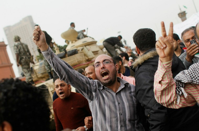 January 29, 2011: Egyptians march against President Hosni Mubarek near Egyptian Army tanks in Tahrir Square in Cairo, Egypt. Tens of thousands of demonstrators have taken to the streets across Egypt in Cairo, Suez, and Alexandria to call for the resignation of President Hosni Mubarak. Riot police and the Army have been sent into the streets to quell the protests, which so far have claimed at least 38 lives and left more than a two-thousand injured. (Chris Hondros/Getty Images)