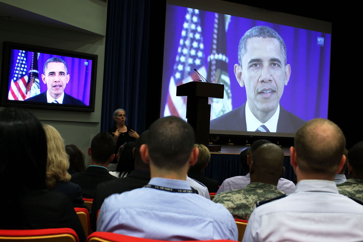 """Washington D.C.: Members of the audience watch a video message from U.S. President Barack Obama during an event to observe the """"Lesbian, Gay, Bisexual and Transgender Pride Month"""" June 26, 2012 at the Pentagon in Arlington, Virginia. It was the first-ever LGBT event held at the Pentagon. (Alex Wong/Getty Images)"""