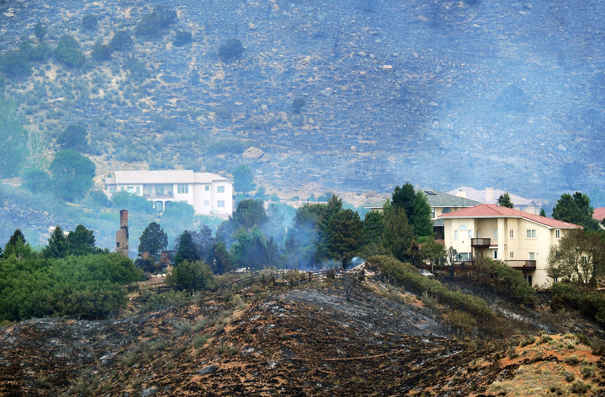 JUNE 27: A chimney from a burned home stands next to untouched homes from the Waldo Canyon fire on June 27, 2012 in Colorado Springs, Colorado. The fire burned numerous homes yesterday as it expanded to 15,000 acres and over 32,000 people have been evacuated. (Chris Schneider/Getty Images)