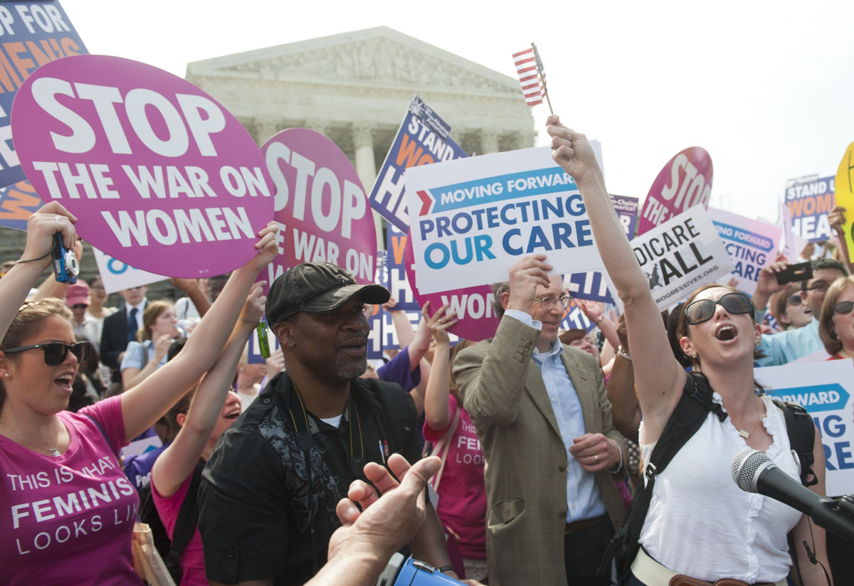 June 28, 2012: Supporters of US President Barack Obama's signature healthcare legislation celebrate after the US Supreme Court upheld the constitutionality of the Affordable Healthcare Act, outside the Supreme Court in Washington, DC, June 28, 2012. The Court upheld the reform but changed some of the key provisions, in a major election-year victory for President Obama. The nation's top justices ruled that a key plank of Obama's domestic policy to extend health insurance to some 32 million Americans was constitutional, but imposed some limitations on extending aid to the nation's poorest. (Saul Loeb/AFP/Getty Images)