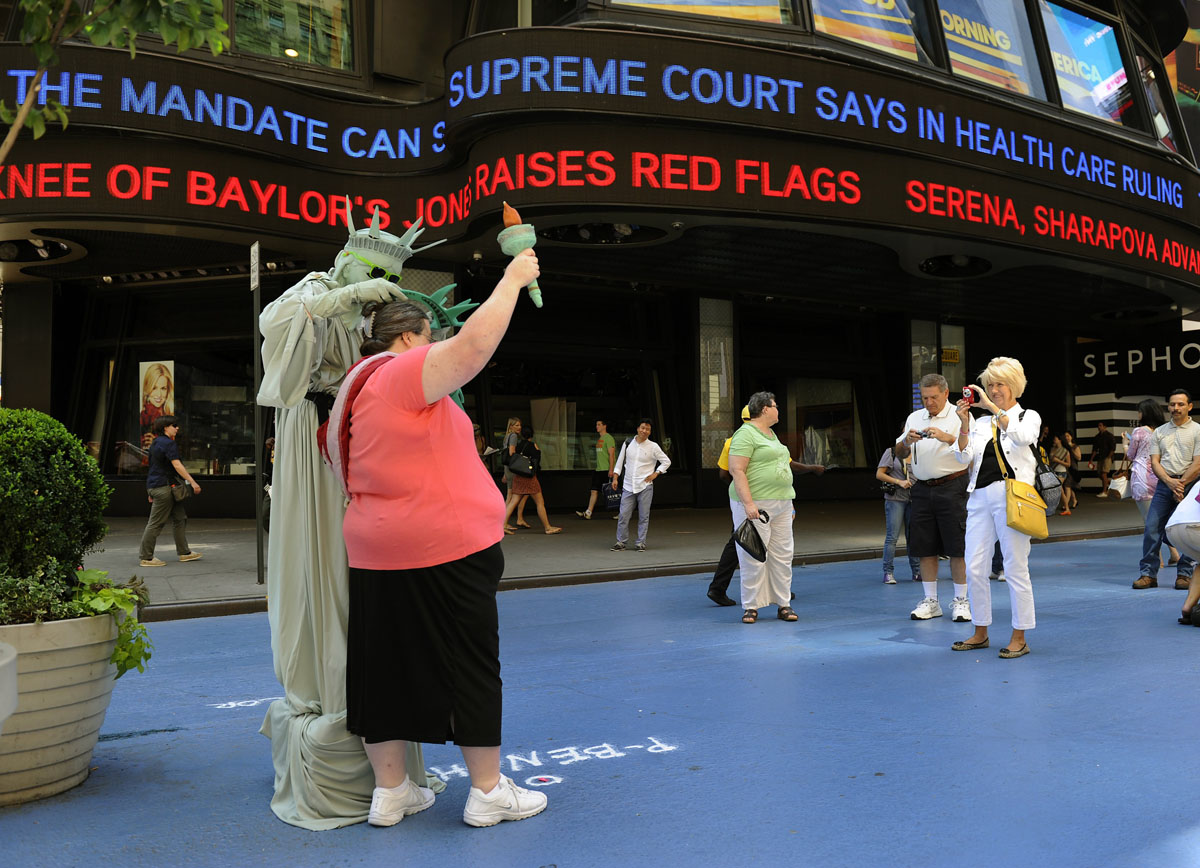 June 28, 2012: A woman poses for pictures with a man dressed as the Statue of Liberty as the ABC Television Times Square Studios tickertape reports the news on the US Supreme Court ruling on health care reform on June 28, 2012. in a 5-4 ruling, the Supreme Court upheld US President Barack Obama's health care reforms to insure another 32 million Americans, in a major victory for the president in the heat of a tight re-election contest. (Timothy A. Clary/AFP/Getty Images)