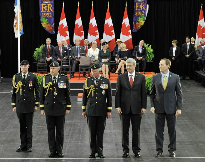 May 22, 2012: (2nd L- R) Canadian Equerry, General Walter Natynczyk, Prince Charles, Prince of Wales, Canadian Prime Minister Stephen Harper, and Canadian Defence Minister Peter MacKay participate in the 1812 presentation of a commemorative medal and banner for the 1812 Commemorative Military Muster hosted by the Government of Canada at Fort York Armoury, as part of the Royal visit to Canada to mark the Queen's Diamond Jubilee in Toronto, Canada. (Jag Gundu/Getty Images)