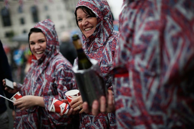Revelers brave the rain, with champagne, to watch the Royal Pageant pass Blackfriars Bridge on June 3, 2012 in London, England. (Matthew Lloyd/Getty Images)