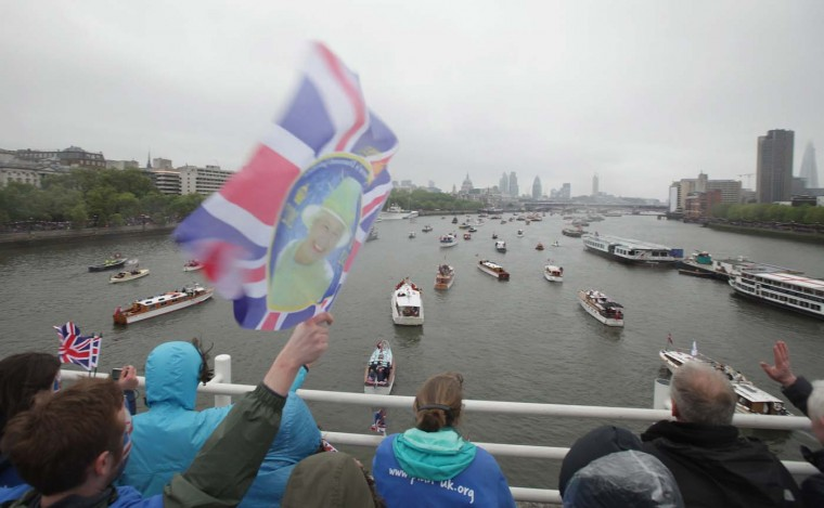 Spectators stand on Waterloo Bridge over the Thames while watching the River Pageant of the Diamond Jubilee in the rain on June 3, 2012 in London, England. (Sean Gallup/Getty Images)