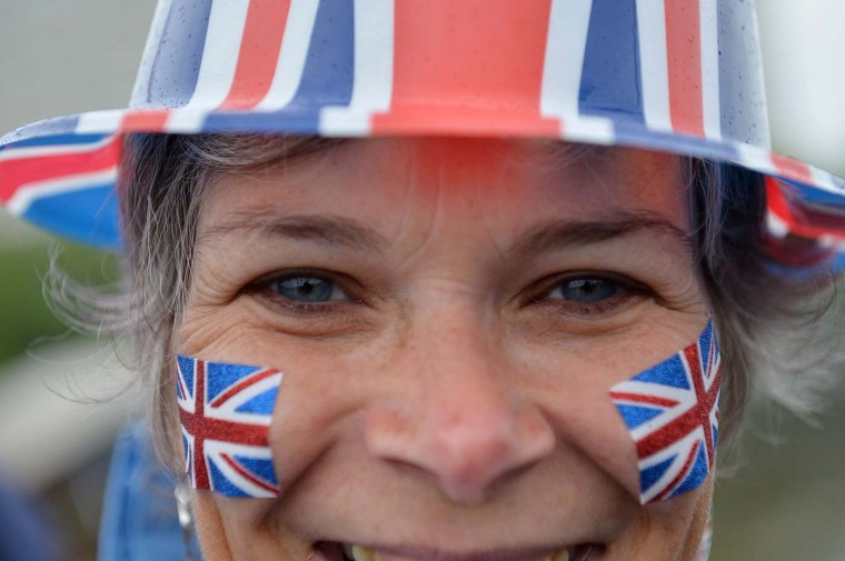 A spectator on Westminster Bridge watches the River Pageant of the Diamond Jubilee on June 3, 2012 in London, England. (Jeff J Mitchell/Getty Images)