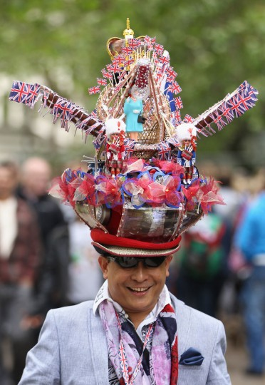 A visitor arrives wearing a hat decorated with a crown, British flags, dolls and an effigy of Queen Elizabeth II, at St. James Park prior to the Diamond Jubilee concert at Buckingham Palace on June 4, 2012 in London, England. (Sean Gallup/Getty Images)