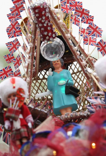 An effigy of Queen Elizabeth II peeks out from a hat decorated with a crown, British flags, and dolls on the head of a visitor prior to the Diamond Jubilee concert at Buckingham Palace on June 4, 2012 in London, England. (Sean Gallup/Getty Images)