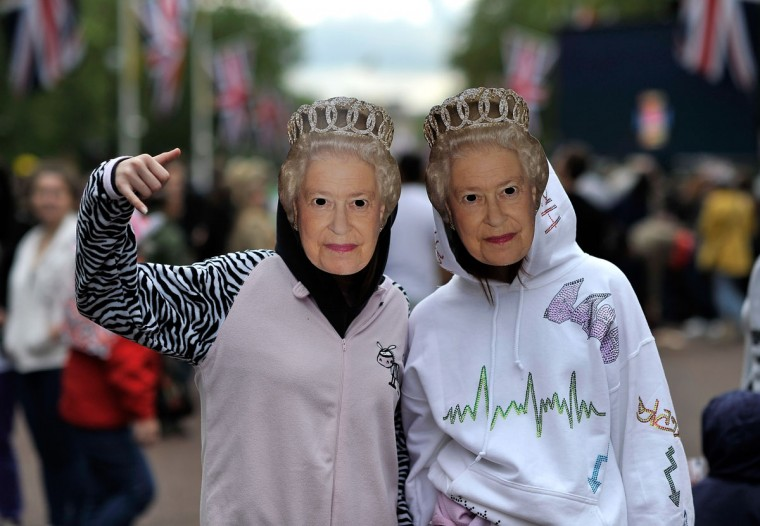 People pose wearing masks of Queen Elizabeth II in St James's Park prior to the Diamond Jubilee Buckingham Palace Concert on June 4, 2012 in London, England. (Gareth Cattermole/Getty Images)