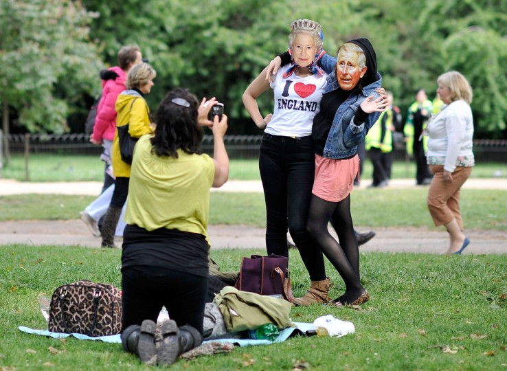 People pose wearing masks of Prince Charles, Prince of Wales and Queen Elizabeth II in St James's Park prior to the Diamond Jubilee Buckingham Palace Concert on June 4, 2012 in London, England. (Gareth Cattermole/Getty Images)