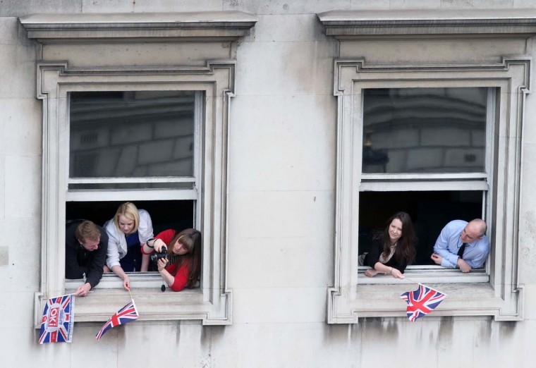 People wave the British flag outside windows while trying to view the procession of the Royal family driving along in carriages on June 5, 2012 in London, England. (Elizabeth Dalziel/WPA Pool/Getty Images)