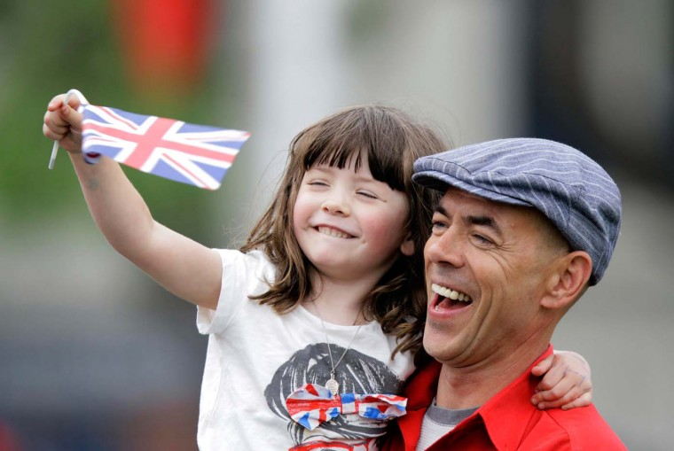 A man holds a young girl with a flag as crowds line Parliament Street to watch the Royal Motorcade passing by on June 5, 2012 in London, England. (Kevin Coombs/WPA Pool /Getty Images)