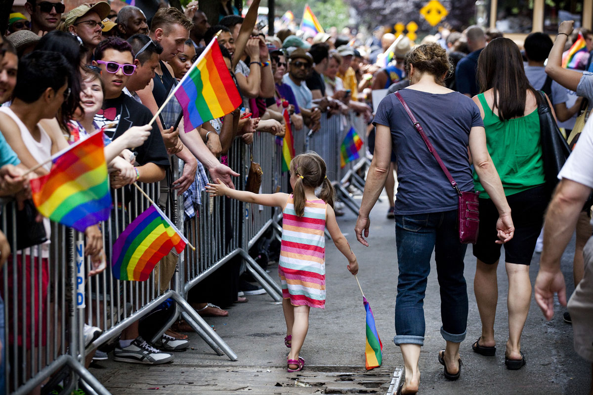 New York: A girl hi-fives reveler as she marches in the Gay Pride March on June 24, 2012. The annual civil rights demonstration commemorates the Stonewall riots of 1969, which erupted after a police raid on a gay bar, the Stonewall Inn on Christopher Street. (Michael Nagle/Getty Images)
