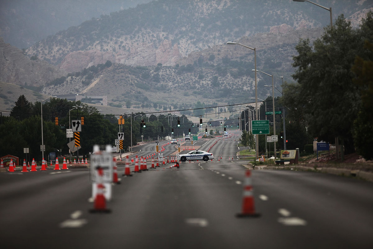 JUNE 28: A police road block in an evacuated neighborhood near the Waldo Canyon fire is viewed on June 28, 2012 in Colorado Springs, Colorado. The massive fire, which eased slightly with the help of cooler temperatures and lighter winds, has destroyed hundreds of homes and forced more than 35,000 people to flee. (Spencer Platt/Getty Images)