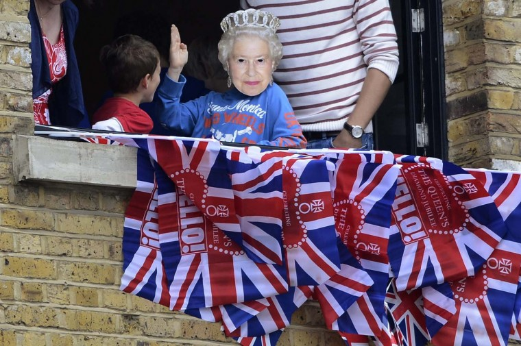 A boy wears a mask portraying Britain's Queen Elizabeth while waiting near Tower Bridge for the start during the Diamond Jubilee river Pageant in London on June 3, 2012. (Dylan Martinez/AFP/Getty Images)