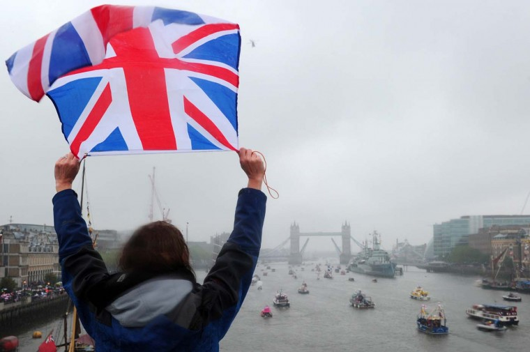 A woman waves Britain's Union flag while watching the Thames Jubilee Pageant in London, on June 3, 2012. (Carl Court/AFP/Getty Images)
