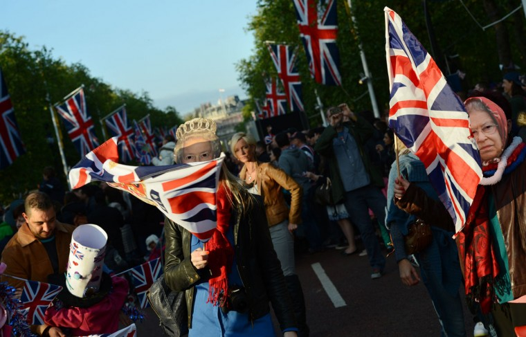 Spectators wearing Queen Elizabeth masks cheer with Britain's Union flags during the Queen's jubilee concert on the Mall outside Buckingham Palace in London, on June 4, 2012. (Adrian Dennis/AFP/Getty Images)