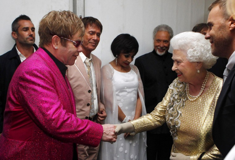 Queen Elizabeth II meets Sir Elton John backstage as British singer Robbie Williams (R) watches during the Diamond Jubilee Concert outside Buckingham Palace in London, on June 4, 20112. (Dave Thompson/AFP/Getty Images)