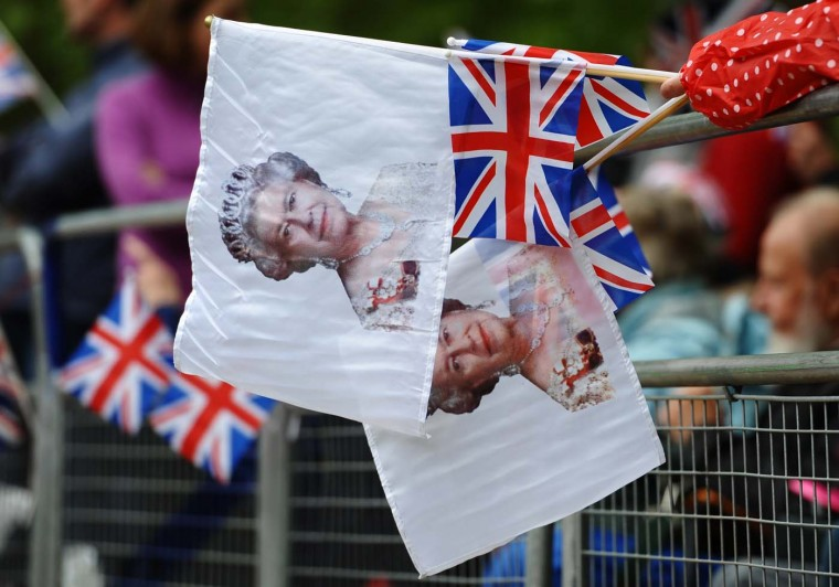A royal supporter holds Queen Elizabeth and Union flags as people wait on the Mall for the carriage procession of the Queen's Diamond Jubilee in London on June 5, 2012. (Paul Ellis/AFP/Getty Images)