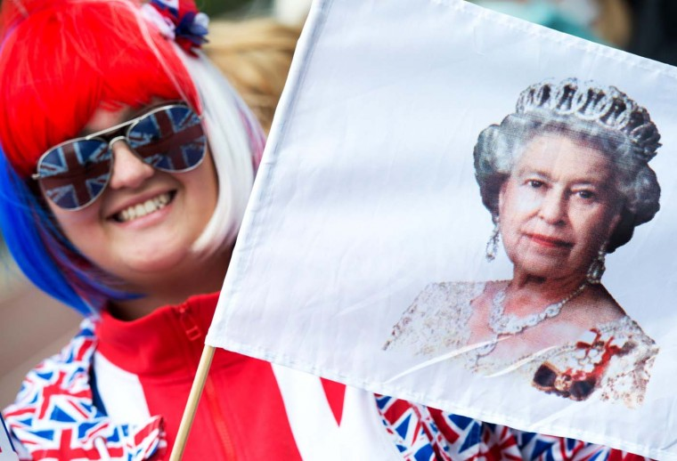 Elise Pearce holds a flag showing Britain's Queen Elizabeth II while waiting for the carriage procession on The Mall during the Diamond Jubilee in London, on June 5, 2012. (Adrian Dennis/AFP/Getty Images)